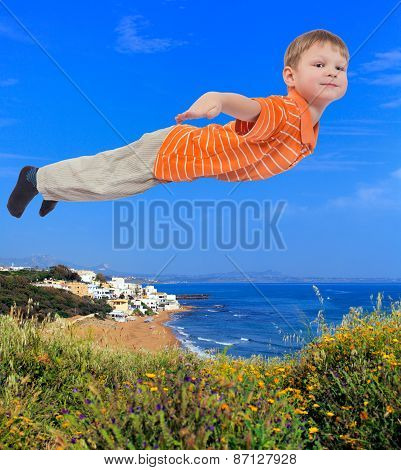 Young boy flying over sea shore in background