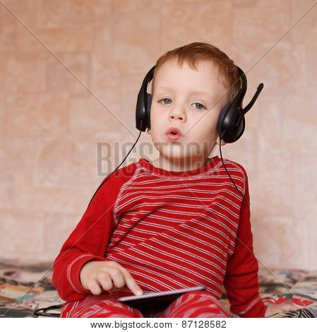 Little Boy With Headphones At Home