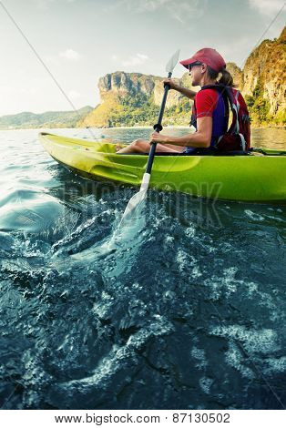 Young lady paddling hard the sea kayak