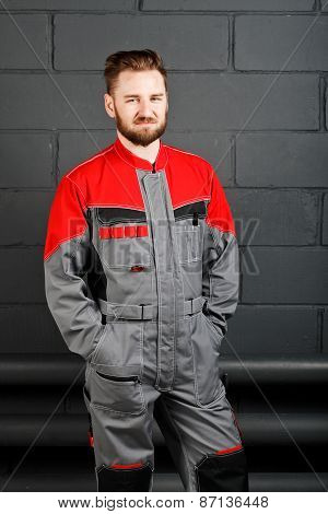 Portriat Of Smiling Man Wearing Overalls Near Brick Wall