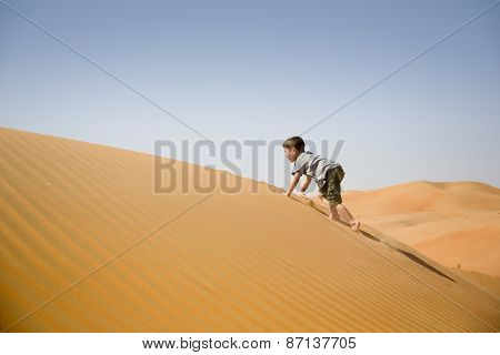 Young boy plays among sand dunes in desert
