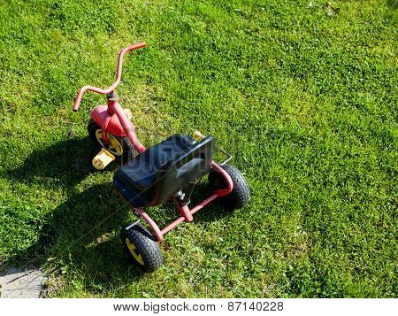 Childhood. Small Red Tricycle Cycle Toy On Grass.