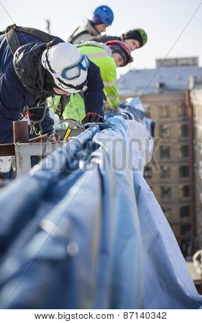 Industrial climbers working on roof of building