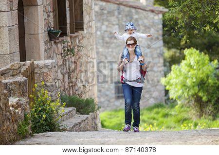 Caucasian woman tourist carrying her little son