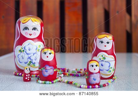 Five Dolls And Colored Beads On The Table
