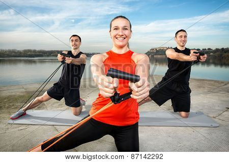 Young sporty people with stretching band