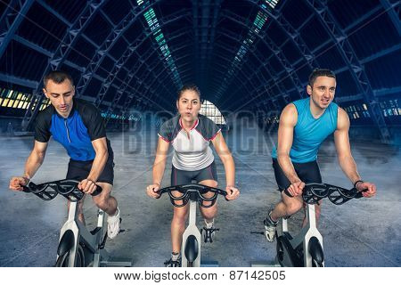 group of three people exercise on bike, spinning class,