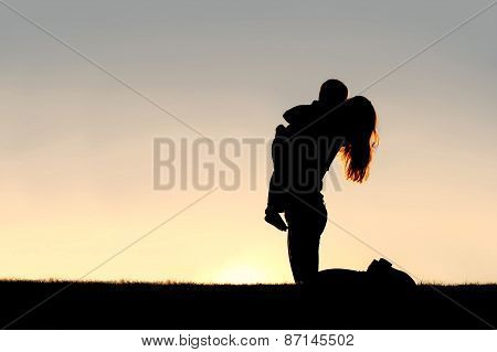 Silhouette Of Happy Mother Playing Outside With Young Child