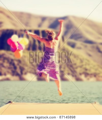 a carefree young woman jumping on a dock with balloons toned with a retro vintage instagram filter effect app or action