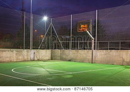 Basketball court illuminated at dusk