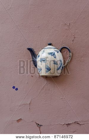 Old teapot with insects pattern on facade of old building in Vilnius, Lithuania.