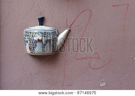 Ancient teapot embedded in facade of old building in Vilnius, Lithuania.