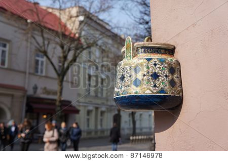 Ancient teapot embedded in facade of old building in Vilnius, Lithuania. Inscription on the teapot is address of this building - Bernardine street 2.