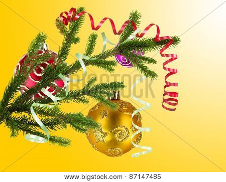 Christmas Balls Hanging With Ribbons On Fir Tree Over Yellow