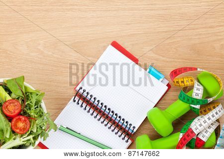Healthy food, dumbells, tape measure and notepad for copy space. Fitness and health