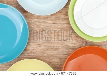 Colorful plates and saucers over wooden table background. View from above with copy space