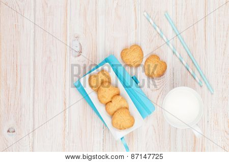 Cup of milk, heart shaped cookies and notepad on white wooden table with copy space