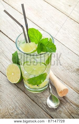 Fresh mojito cocktail and bar utensils. On wooden table