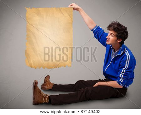 Handsome young man presenting old paper copy space