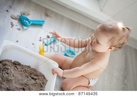 Little Girl Playing With Sand On Floor