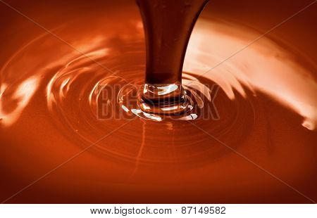 Chocolate flow. Close up of liquid hot chocolate pouring closeup. Chocolate swirl