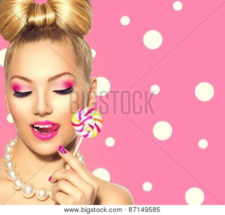 Beauty fashion model girl Eating colourful lollipop. Young funny woman with bow hairstyle, pink nail art and makeup over polka dots background