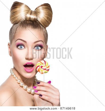 Beauty fashion model girl Eating colourful lollipop. Surprised Young funny woman with bow hairstyle, pink nail art and makeup isolated on white background