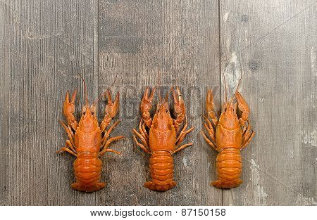 Three Red Crayfishes In A Row On Old Wooden Table