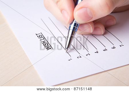 Close Up Of Female Hand Writing Her Wish List