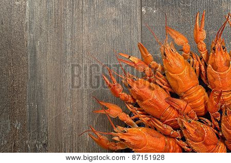 Plate Of Red Crayfishes On Old Wooden Table In Left-bottom Corner