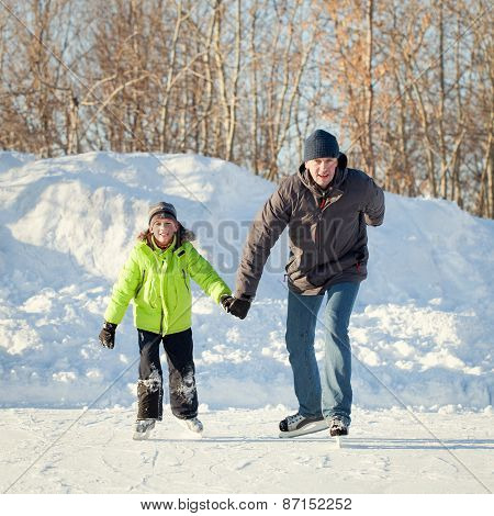 Happy fun father and son learning to skate winter outdoor
