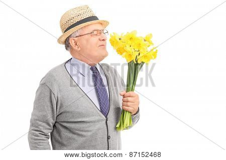 Studio shot of a senior gentleman smelling a bunch of yellow tulips isolated on white background