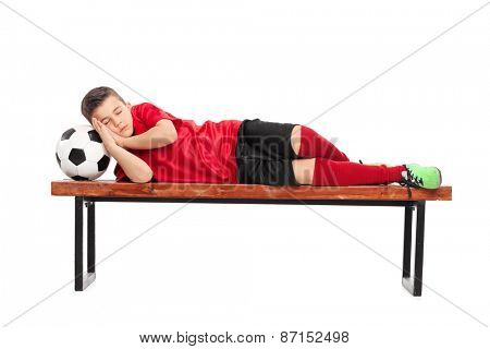 Studio shot of a kid in a football uniform sleeping on a wooden bench isolated on white background
