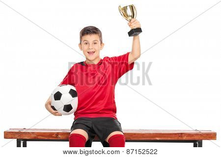 Delighted boy in soccer dress holding a trophy in one hand and a ball in the other, seated on a wooden bench isolated on white background