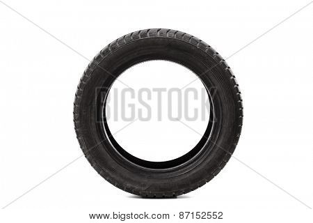 Front view studio shot of a single car tire isolated on white background