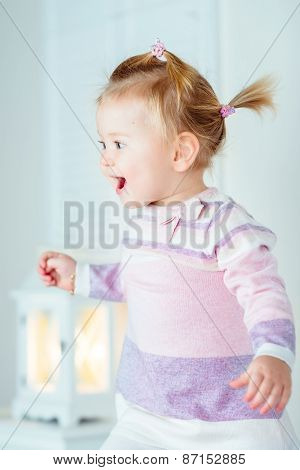 Excited Blond Little Girl With Ponytail Jumping On Bed, Laughing And Screaming