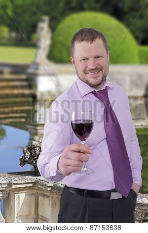 Businessman holding glass of wine with beautiful park in background