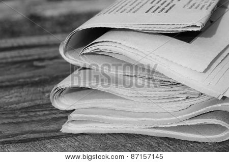 Newspapers on old wood background. Black and white shot.