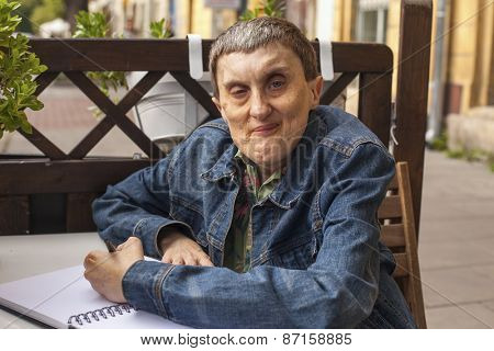 Elderly disabled man with cerebral palsy writing in notebook.