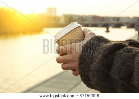 Paper coffee cup in man's hands on street and sunset on background