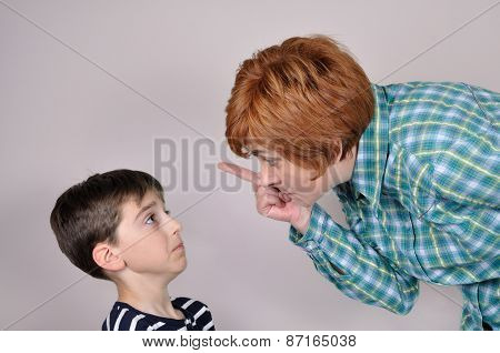 Woman scolding a scared young boy