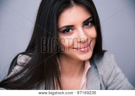 Closeup portrait of a smiling cute woman over gray background. Looking at camera