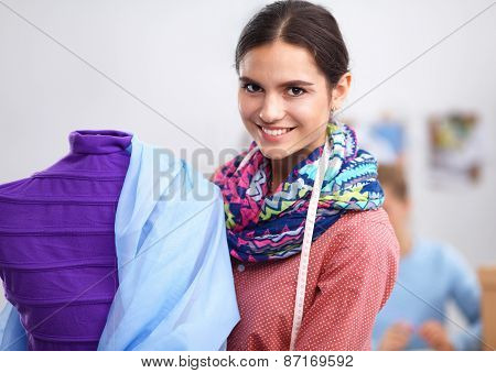 Smiling fashion designer standing near mannequin in office