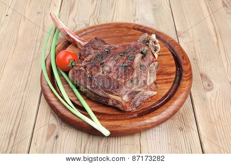 meat savory : grilled beef ribs served with green chives and cherry tomato over wood