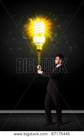 Businessman hold a shining eco-friendly idea bulb on a black background