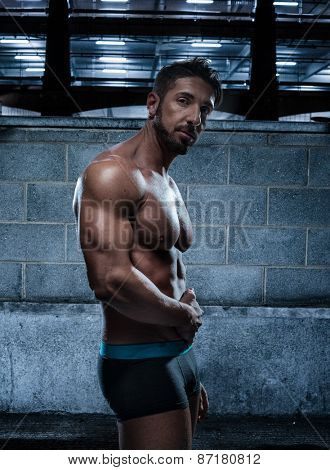 Portrait of a Handsome Muscular Man Wearing Boxer Brief Standing Inside an Old Building While Looking at Camera.