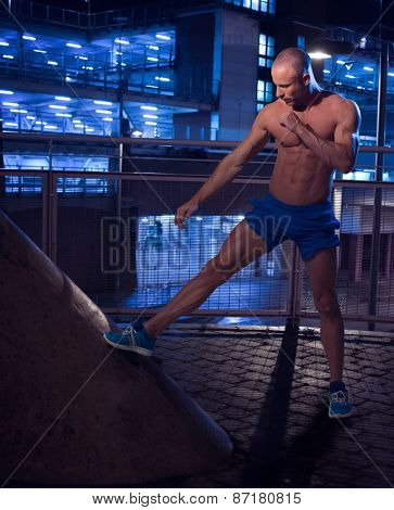 Topless Muscular Bald Man Standing Inside a Building While Stretching his Leg Seriously.