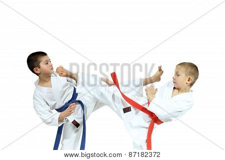Two athletes in karategi are beating blows Yoko geri
