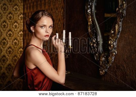 Romantic young woman in evening dress posing in vintage interior. Classic luxurious interior. Fashion shot.
