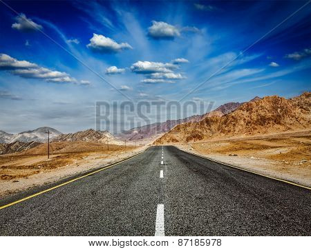 Travel forward concept background - road in Himalayas with mountains and dramatic clouds. Ladakh, Jammu and Kashmir, India